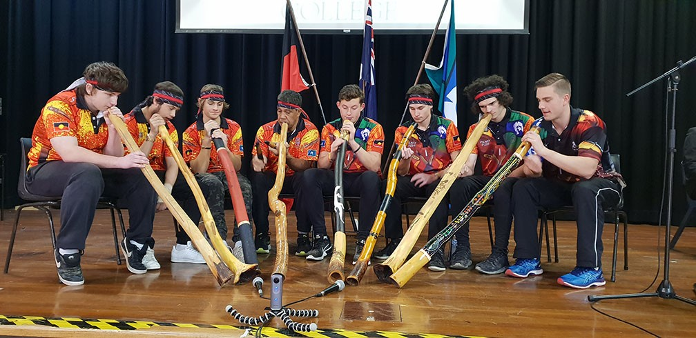 Many students playing the didgeridoo