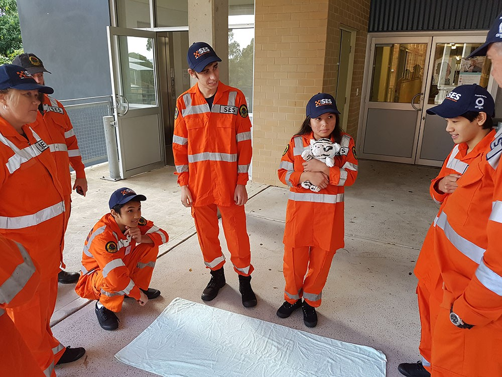 5 students dressed in high visibility orange gear listening to a SES Instructor
