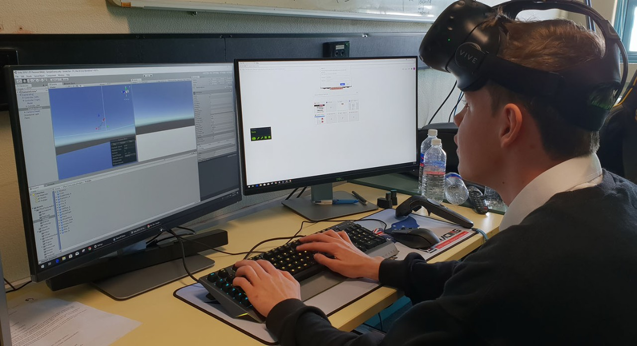 Student working on a computer with Virtual Reality headset